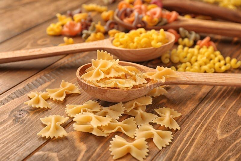 Cuillères avec différents types de pâtes crues sur la table en bois photographie stock libre de droits