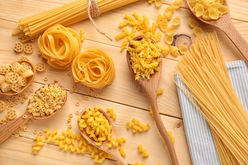 Cuillères avec différents types de pâtes crues sur la table en bois images libres de droits