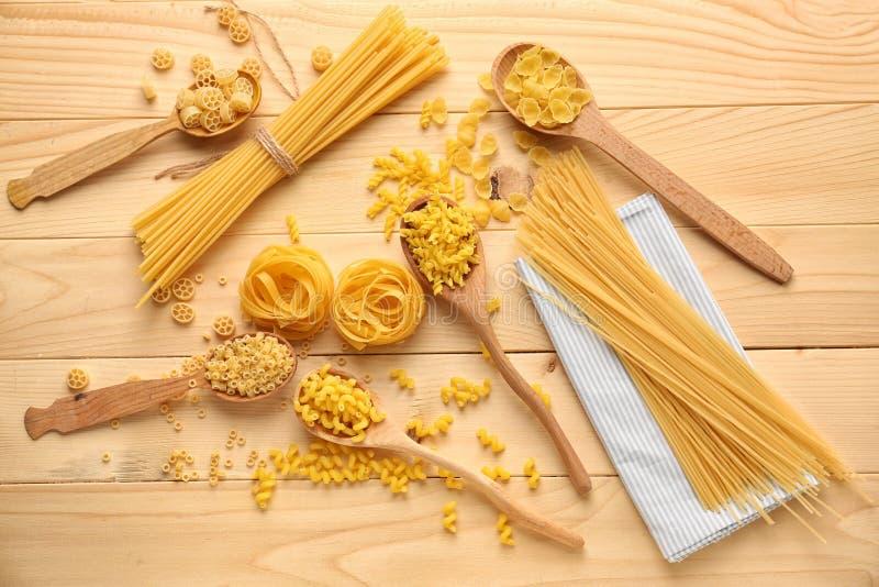 Cuillères avec différents types de pâtes crues sur la table en bois photographie stock