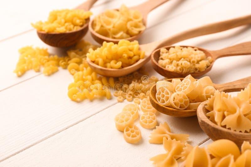 Cuillères avec différents types de pâtes crues sur la table en bois blanche images libres de droits