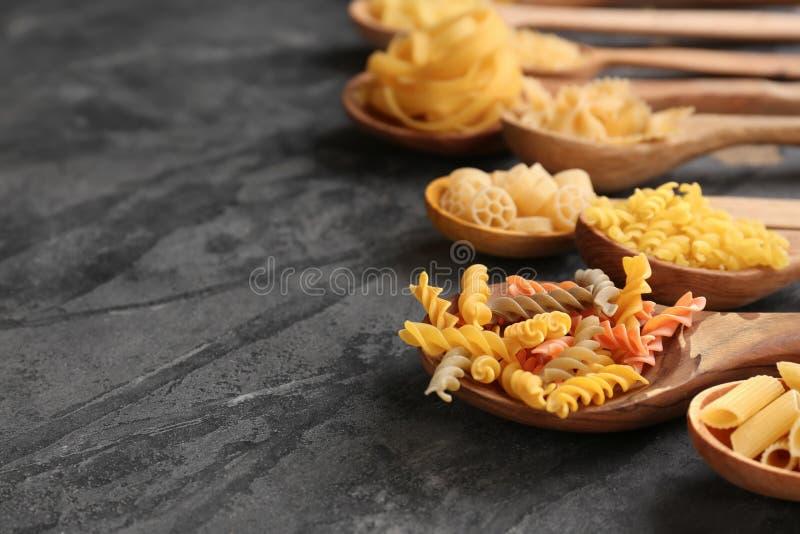 Cuillères avec différents types de pâtes crues sur la table grise photos libres de droits