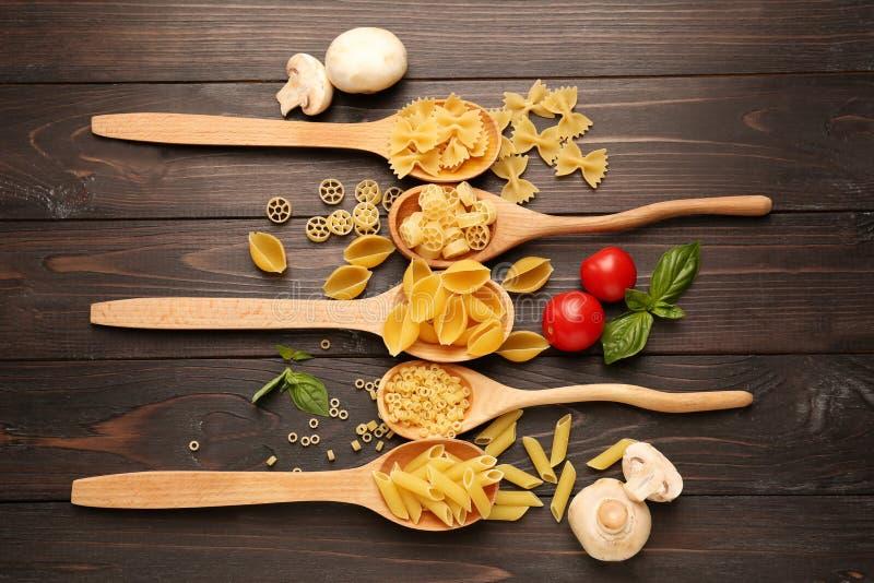 Cuillères avec différents types de pâtes crues sur le fond en bois images stock