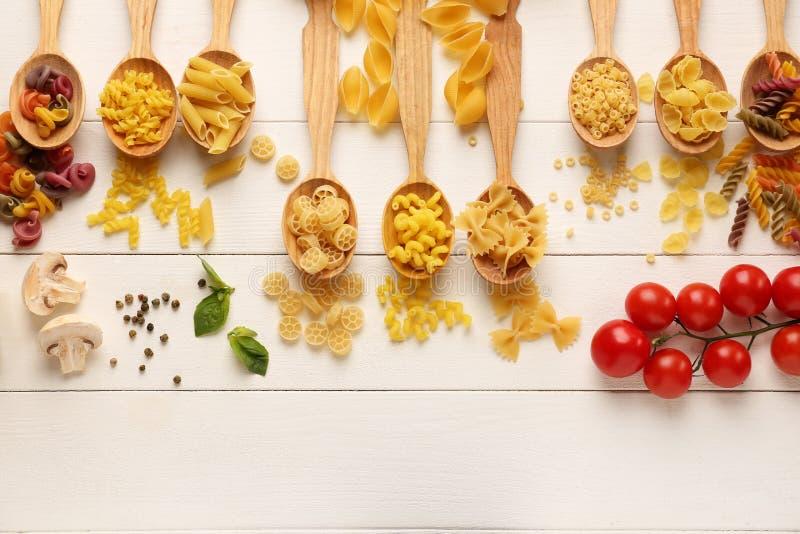 Cuillères avec différents types de pâtes crues sur le fond en bois blanc photo stock