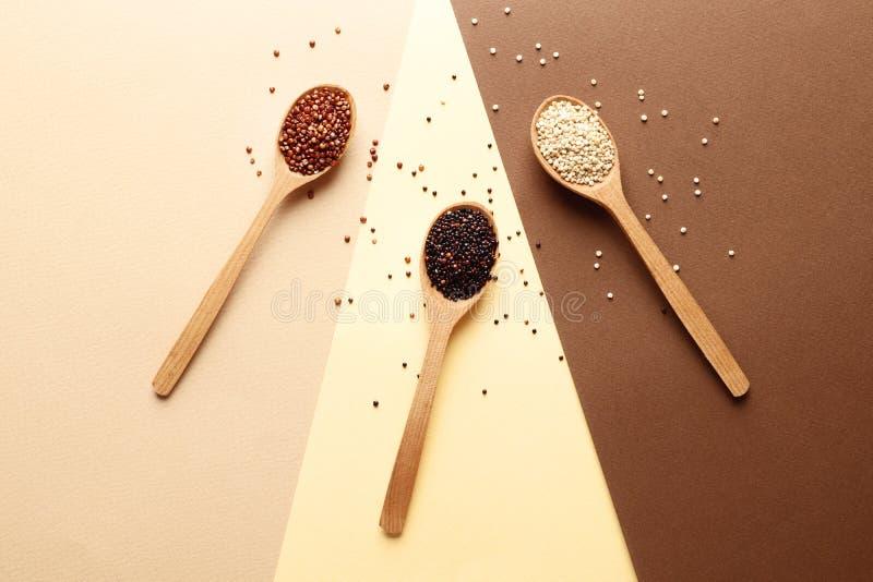 Cuillères en bois avec différents types de quinoa et d'espace pour le texte sur le fond de ? images stock