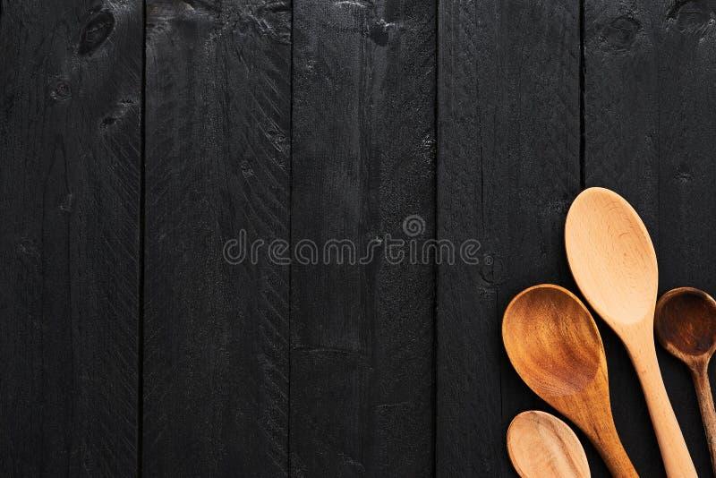 Cuillères en bois sur le fond en bois noir photographie stock libre de droits