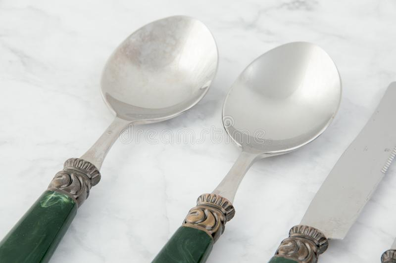 Cuillères et knif sur le fond gris blanc photographie stock