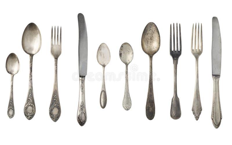 Cuillères, fourchettes et couteaux de cru d'isolement sur un fond blanc photographie stock libre de droits