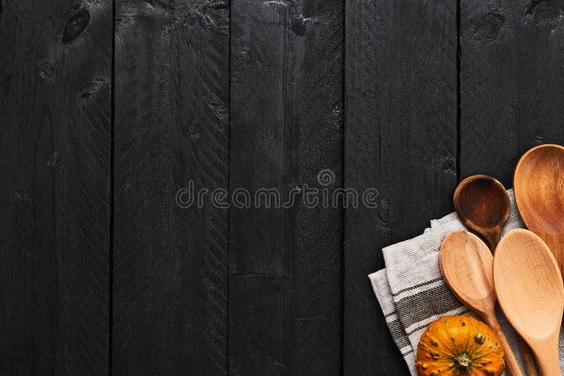 Cuillères, potiron et dishtowel en bois sur le fond en bois noir image stock