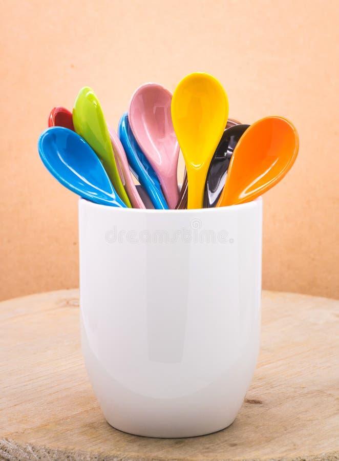 Cuill?re de c?ramique de couleurs dans la tasse sur les contextes en bois Concept color? photographie stock