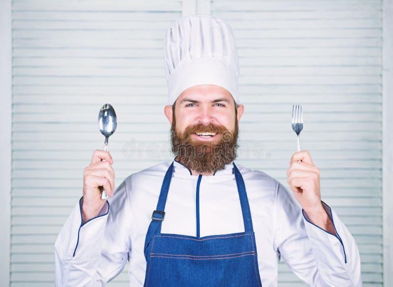 Cuill?re et fourchette de sourire heureuses de prise de visage de chef L'homme beau avec la barbe tient la vaisselle de cuisine s photographie stock