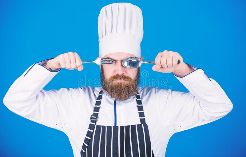 Cuill?re et fourchette strictes s?rieuses de prise de visage de chef Concept de proc?d? de cuisson Laisse le plat d'essai Chef af photos stock