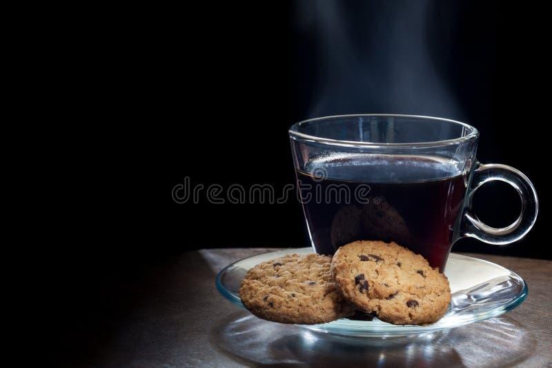 Cuire le café à la vapeur noir chaud avec des gâteaux aux pépites de chocolat image libre de droits