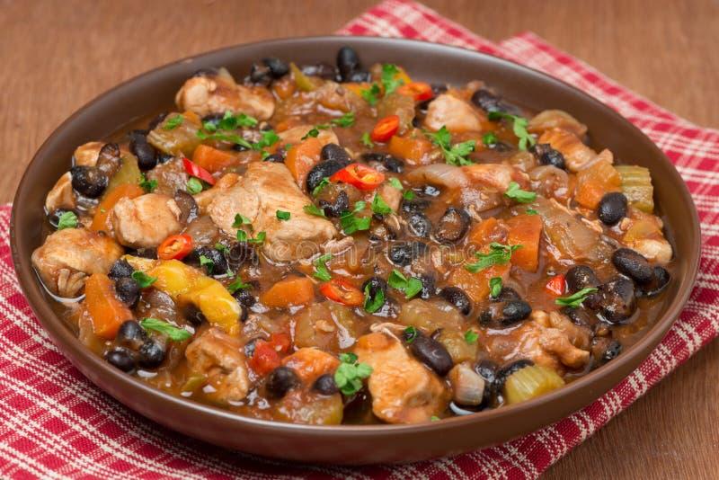 Cuisez avec les haricots noirs, le piment, le poulet et les légumes, plan rapproché images stock