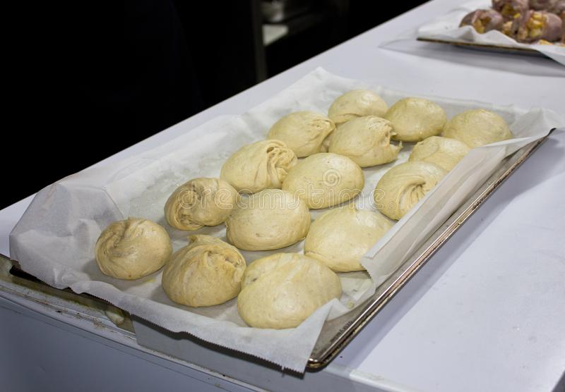 Cuisez les petits pains à la vapeur de la pâte de blé de levure sur un plateau images libres de droits