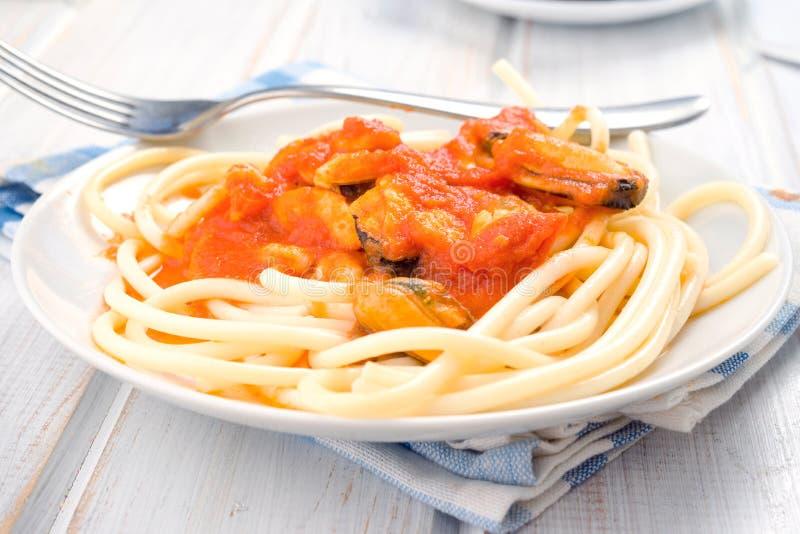 Cuisez les spaghetti faits maison avec des crevettes roses et des moules dans le plat blanc photo stock