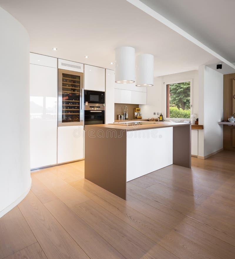 Cuisine avec l'île blanche avec le capot et projecteurs en appartement moderne photos libres de droits