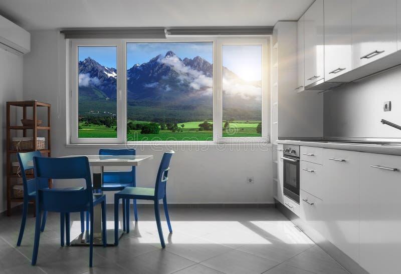 Cuisine avec les meubles et les fenêtres blancs avec le paysage de montagne photo stock