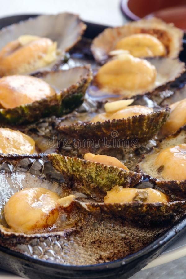 Cuisine of the Azores. The mollusks of Lapas, Limpets are popular as a snack in the Azores. Fried clams in garlic butter in a black frying pan. Traditional stock images
