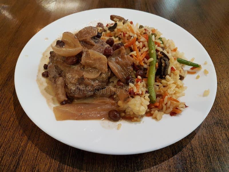 Cuisine baltique, côtelette de viande avec des raisins secs et riz avec des légumes photo libre de droits