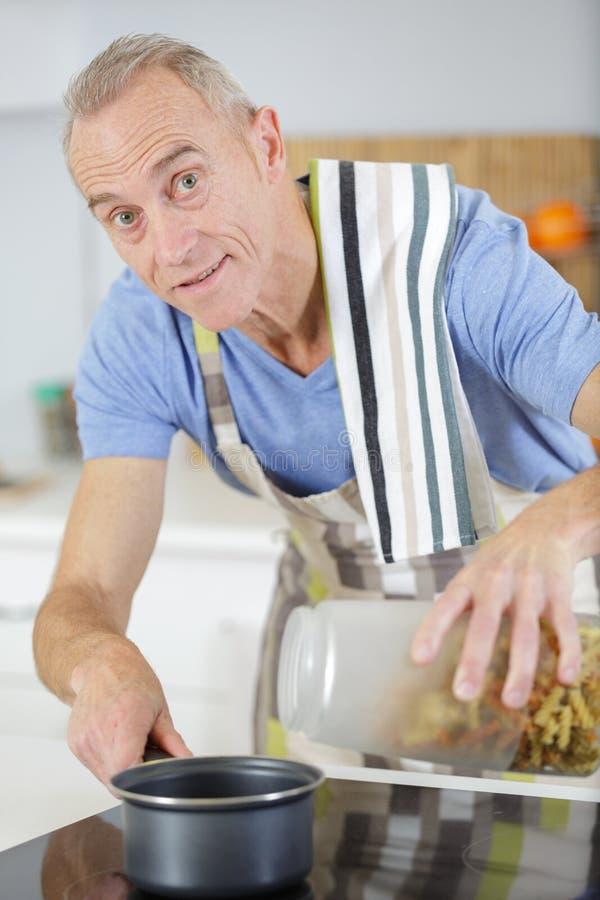 Cuisine d'homme mûr et pâtes à bouillir photographie stock libre de droits