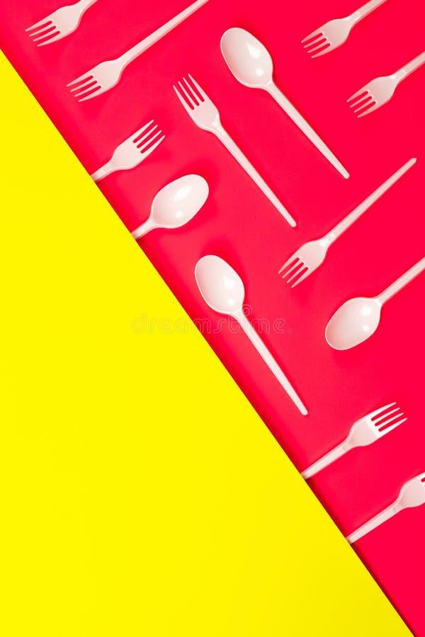 Cuisine en plastique, fourchettes, cuillères sur rose néon photos libres de droits