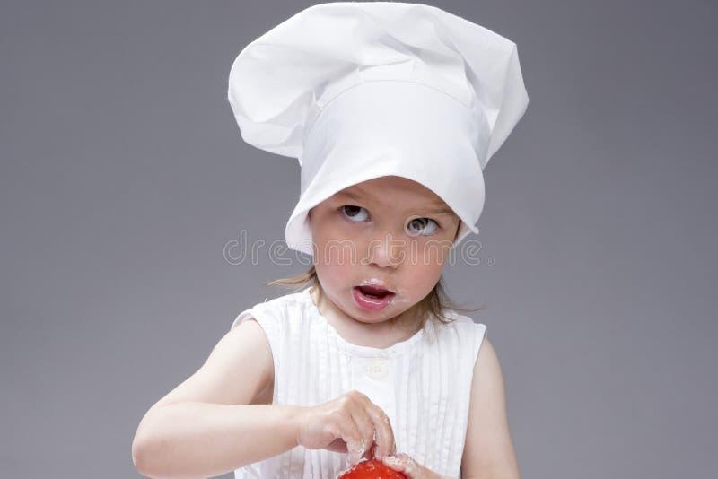 Cuisine et concepts et idées de cuisson Portrait de la belle fille caucasienne mignonne posant en tant que cuisinier Contre Gray  images stock