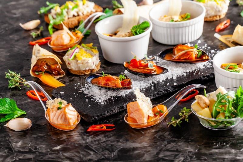 Cuisine européenne apéritif pour le vin sur un fond noir Pâté, mini salade, canape, produits de mer, saumons et moules en tomate photographie stock libre de droits