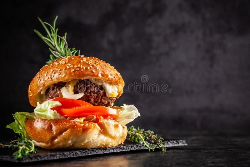 Cuisine familiale américaine un grand hamburger grillé avec la côtelette de porc, tomate, concombre, avec un sésame et un petit p images stock