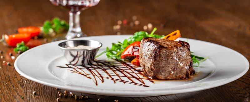 Cuisine géorgienne Bifteck de boeuf juteux, bifteck de veau d'un plat blanc avec la fusée rôtie, légumes grillés et sauce images libres de droits
