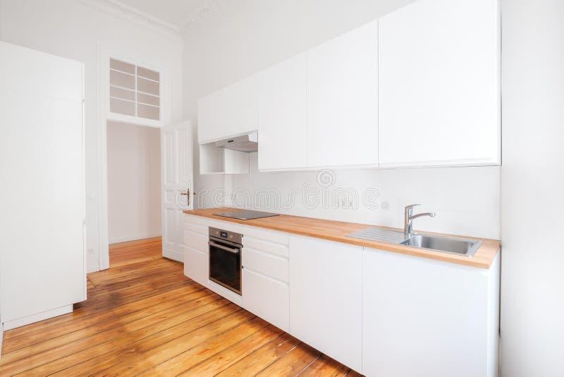 Cuisine intégrée vide et nouvelle avec des meubles de whote et plancher en bois images stock