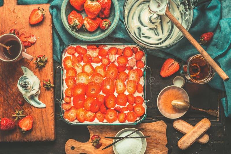Cuisine italienne, préparation de gâteau de tiramisu de fraise avec faire cuire des ingrédients et des outils de cuisine sur le f image libre de droits