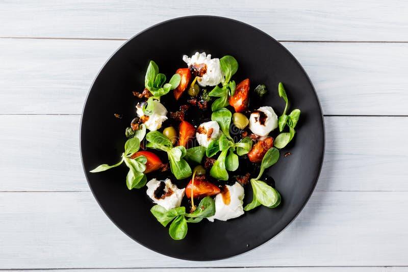 Cuisine italienne Salade caprese italienne fraîche avec du mozzarella et des tomates de plat foncé sur la table en bois blanche V photo stock
