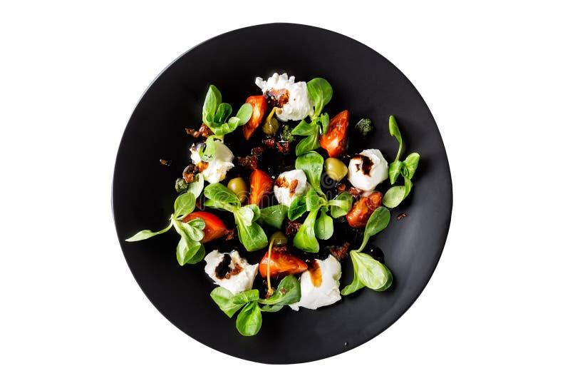 Cuisine italienne Salade caprese italienne fraîche avec du mozzarella et des tomates du plat foncé d'isolement sur le fond blanc  images libres de droits