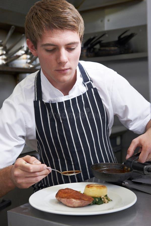 Cuisine masculine de restaurant de Preparing Meal In de chef images stock