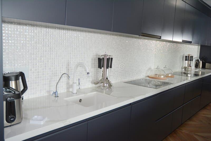 Cuisine moderne avec des tuiles de mosa?que, robinet, capot de cuisine, miroir, four photos libres de droits