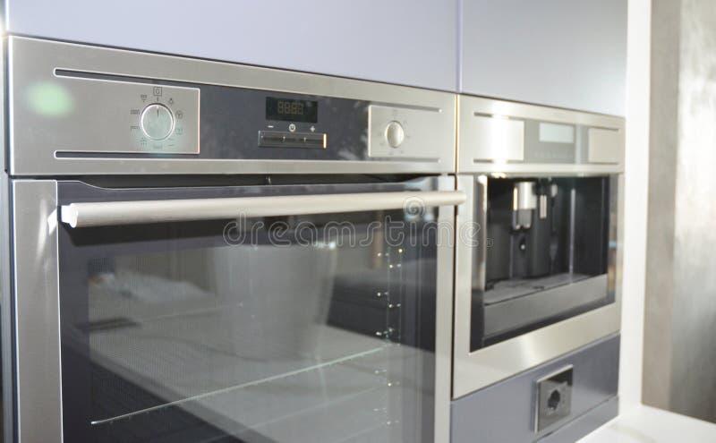 Cuisine moderne avec le four électrique, le fourneau éclectique et la machine de café dans la tache floue légère images stock
