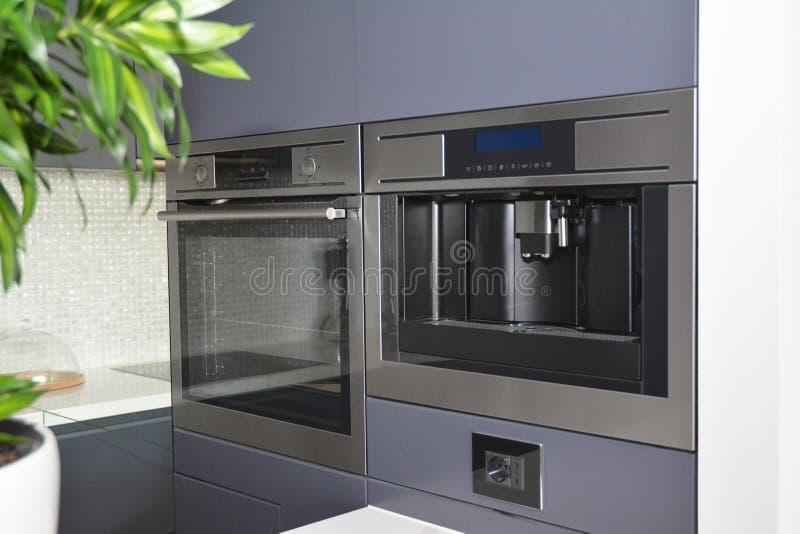 Cuisine moderne avec le four électrique, le fourneau électrique et la machine de café photo libre de droits