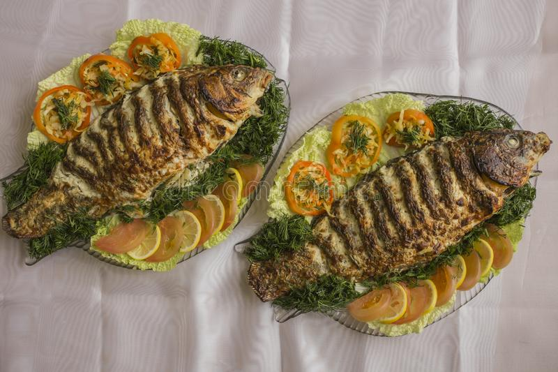 Stuffed carp, decorated with vegetables. Fish dish. royalty free stock images