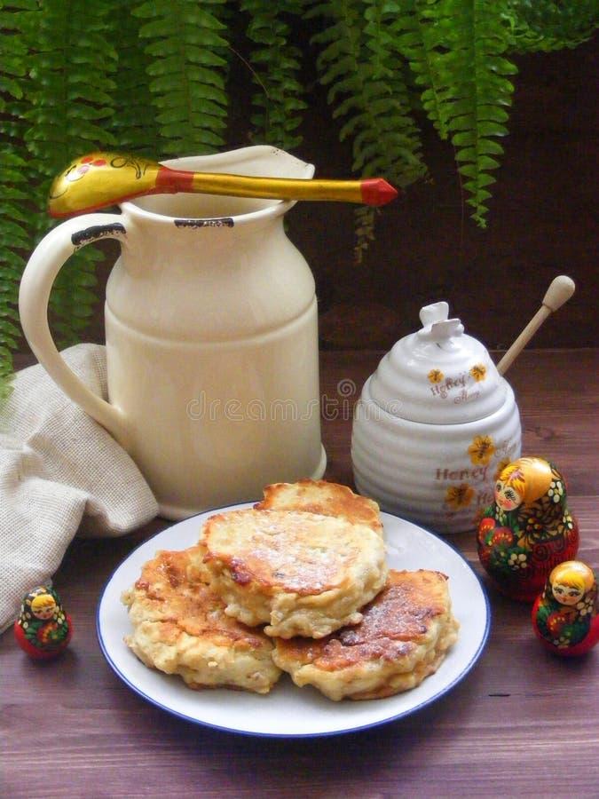 Cuisine russe : crêpes de crêpes de plat avec des flocons de chêne sur le fond en bois brun avec la cruche, le miel et traditionn photographie stock