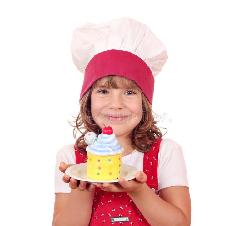 Cuisinière de petite fille avec le petit gâteau coloré photographie stock