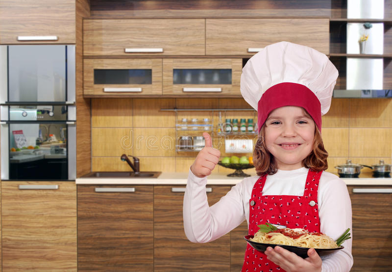 Cuisinière de petite fille avec les spaghetti et le pouce dans la cuisine photos stock