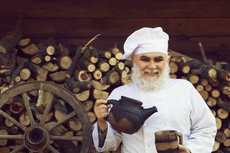 Cuisinier barbu avec la bouilloire et la tasse images stock
