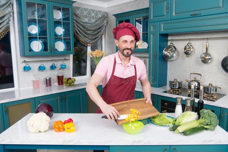 Cuisinier barbu coupant le paprika jaune Le type de sourire dans le chapeau fait la salade avec le paprika image libre de droits