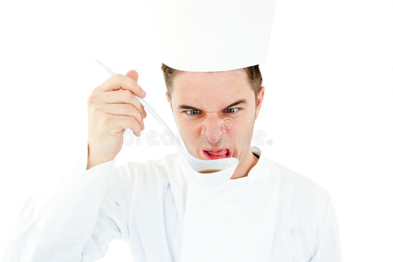 Cuisinier caucasien goûtant un potage faisant une grimace images libres de droits