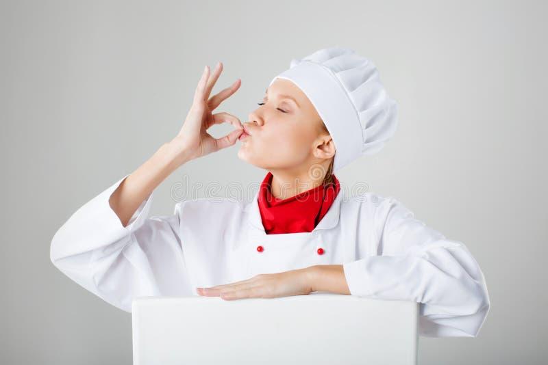 Cuisinier de chef de femme faisant le geste correct avec ses mains après repas de bon goût photo libre de droits