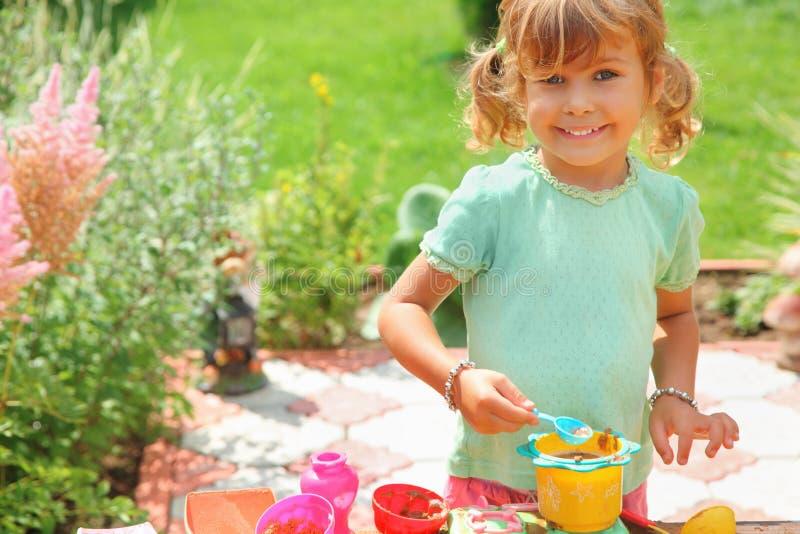 Cuisinier de sourire de pièces de petite fille dans le jardin images stock