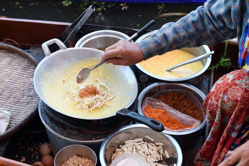 Cuisinier de vendeur de femmes l'omelette thaïlandaise avec des légumes sur le bateau au marché de l'eau photos stock