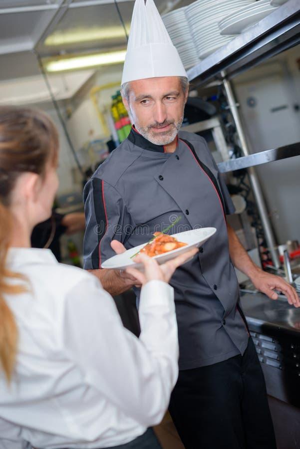 Cuisinier donnant le plat cuisiné image libre de droits