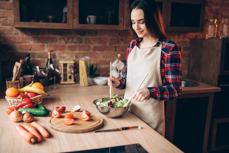 Cuisinier féminin, salade faisant cuire sur la cuisine photographie stock