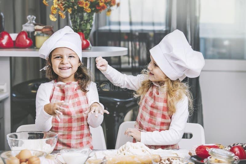 Cuisinier heureux d'enfant de deux petites filles avec de la farine et la pâte aux ventres photographie stock libre de droits